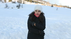 Young woman standing in the snow shivers from the cold. Stock Footage