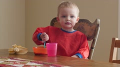 Cute boy eating his banana and cereal for breakfast Stock Footage
