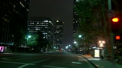A car travels along a street at night in Century City, Los Angeles as seen - stock footage