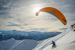 Paraglider launching from snowy slope - stock photo