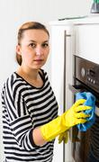 Happy young woman washing furniture at home Stock Photos