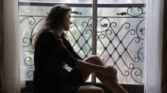 sad and upset young woman sitting near the window : sadness, depression - stock footage