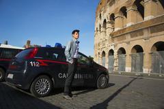 Italian Carabiniere standing alongside a patrol car outside Colosseum in Rome - stock photo