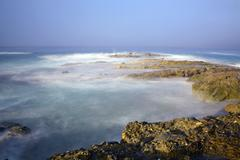 Ocean reef with swirling water - stock photo