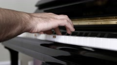 A man playing scales on a piano inside his home Stock Footage