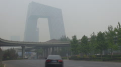 Timelapse traffic street China Central Television building Beijing foggy daytime Stock Footage