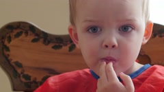 Little boy eating a banana and cereal for breakfast Stock Footage
