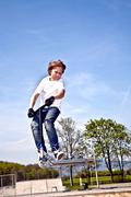 Boy going airborne with a scooter Stock Photos