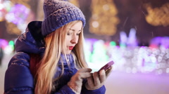 Girl send sms on street evening snowy weather Stock Footage