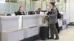 Stock Video Footage of BERLIN, GERMANY: Man at airport information desk at Tegel airport.