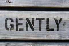 GENTLY stencilled in capitals on wood Stock Photos