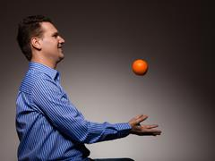 Stock Photo of Diet and healthy nutrition. Man throwing orange
