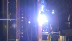 Welder welds structural beams on the scaffolding at night Stock Footage