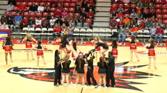 4K college cheerleaders doing a stunt on basketball court Stock Footage
