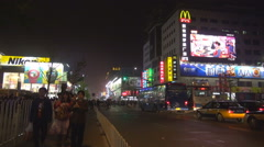 Busy traffic street Beijing commercial district night shop road car congestion Stock Footage