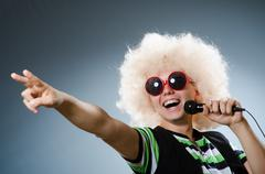 Man in afrowig singing with mic - stock photo