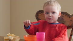 A cute boy eating his banana and cereal for breakfast Stock Footage
