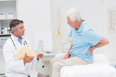 Doctor discussing reports with patient suffering from back pain - stock photo