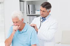 Doctor examining coughing senior patient Stock Photos