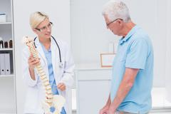 Orthopedic doctor explaining anatomical spine to senior man - stock photo