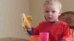 Toddler eating his banana and cereal for breakfast Stock Footage