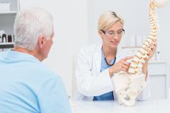 Stock Photo of Doctor explaning anatomical spine to senior patient