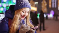 Girl on evening street sending message. Snowy weather. Stock Footage