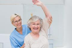Senior patient being assisted by nurse in raising arm - stock photo