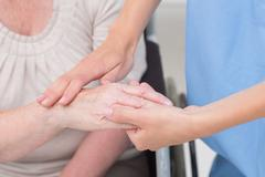 Nurse checking flexibility of patients wrist in clinic - stock photo