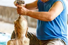 Hand of carver carving wood Stock Photos