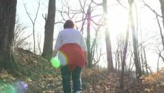 4K rear view of mom and son hiking on trail with sun glare Stock Footage