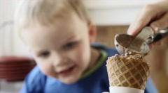 A mother scoops chocolate ice cream into waffle cone Stock Footage