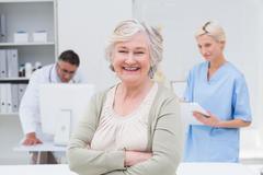 Patient smiling while doctor and nurse working in background Stock Photos