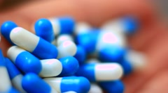 Blue pills in a hand - stock footage