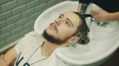 Barber wash customer hair Stock Footage