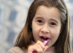 young girl without a tooth while brushing teeth in the bathroom - stock photo