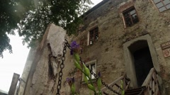Through chain and flowers can be seen in the entrance of an old castle fortress Stock Footage