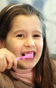 young girl without a tooth while brushing teeth - stock photo