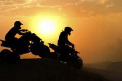 Silhouette ATV or Quad bikes Jump in the sunset. Stock Photos