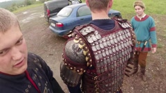 Knights correct each other iron armor against the backdrop of modern cars - stock footage