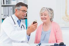 Stock Photo of Doctor showing medicine bottle to female patient