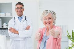 Patient showing thumbs up sign while standing with doctor - stock photo