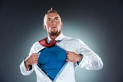 Stock Photo of businessman acting like a super hero and tearing his shirt off
