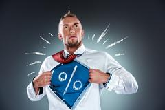 Businessman acting like a super hero and tearing his shirt off Stock Photos