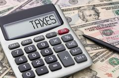 Calculator with money - Taxes - stock photo