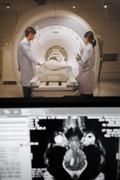 Veterinarian doctor working in MRI scanner room with moniter foreground Stock Photos
