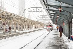 Train Arrives During Heavy Snowfall In Station - stock photo
