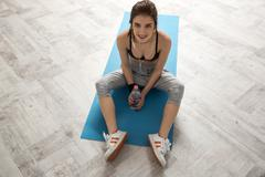 Happy sports woman sitting on the yoga mat and holding bottle of water Stock Photos