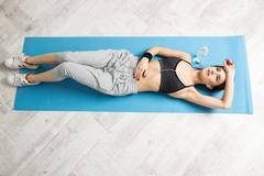 Top view portrait of a young woman lying on the yoga mat at gym - stock photo