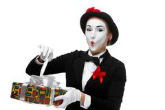 Mime as playful, joyful and excited woman with gift Stock Photos